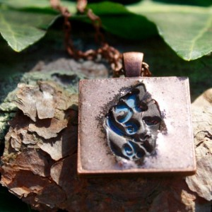 Light blue flower imprinted into copper pendant with necklace