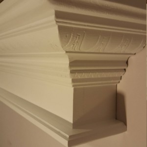 Floating crown molding shelf with decorative design in white