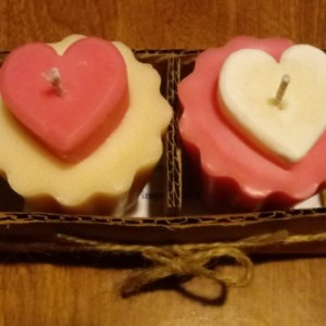 Two 2.5 oz scallop-edged pink and white handmade votive soy wax candles with inset hearts
