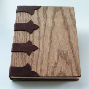 Handmade book, bound in wood, with open stitching onto leather bands.