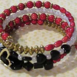 Wire wrapped red and black with gold accent beads bracelet.