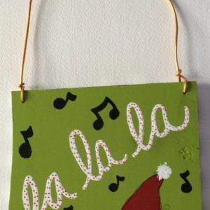 Whimsical Hand Painted Christmas Sign Decoration with Fa La La and Music Notes on Green Background with Santa Hat and Black & White Stripes