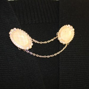 Sweater keeper with rose gold iridescent cameo ends surrounded by rhinestones attached by a gold chain