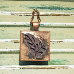 Copper pendant highlighting maroon leaves