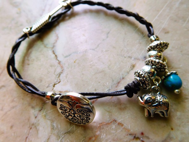 Brown leather braided design bracelet with charms .  #B00213