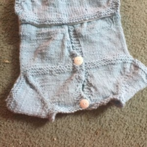 Hand knitted baby onesie