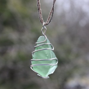 Green rough sea glass pendant wrapped in copper wire on a green brown hemp cord