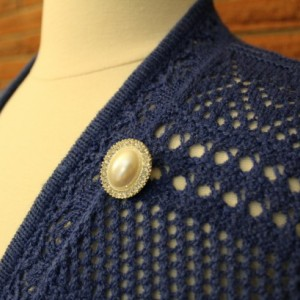Sweater pin with a pearl cameo surrounded by rhinestones