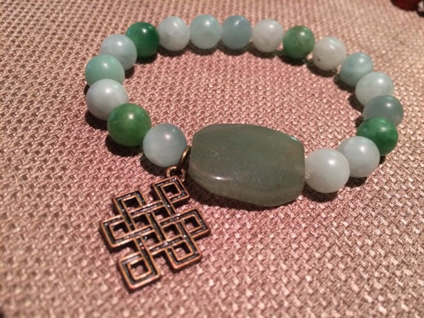 green stretch bracelet with bronze Celtic knot charm