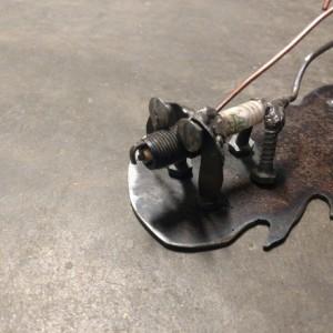 Upcycled sparkplug figure walking a dog