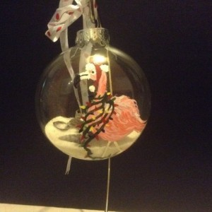 Ornament, glass, pink flamingo with lights draped around his neck and a santa hat.