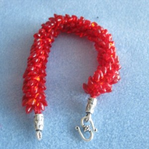 Kumihimo beaded woven bracelet in silver lined red Magatama beads.