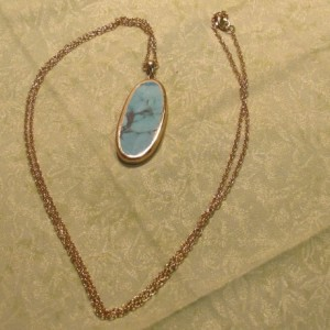 Turquoise pendent with gold accents on a long gold chain.