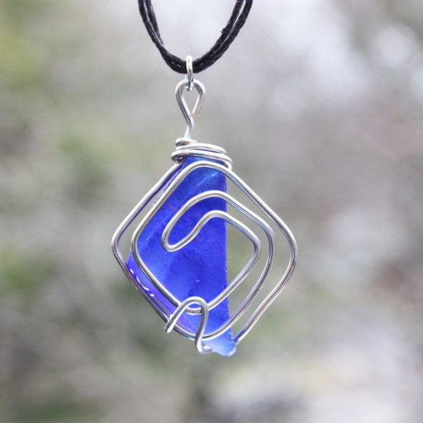 Navy blue sea glass pendant wrapped in copper wire on black hemp cord
