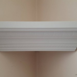 Corner shelf made from decorative crown molding in white