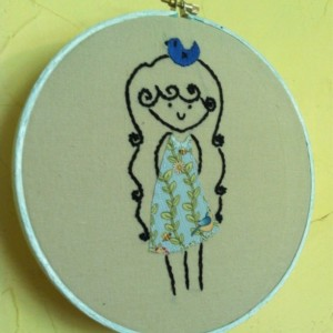 Hoop art embroidery. A girl with a bluebird on her head