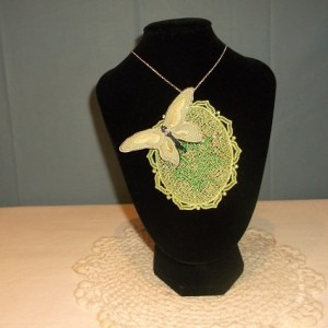 "Machine embroidered cameo necklace with 3-D butterfly. Pat attached her designs onto a 9"" silver chain purchased from Hobby Lobby."