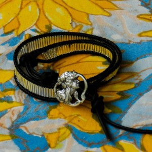 Wrap your wrist in silver bugle beads and black leather and close it with a silver Muse button.
