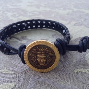 Black crystal wrap bracelet closed with a Medusa gold button.