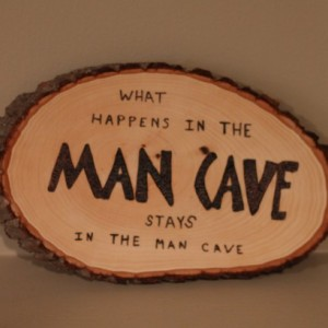 """real wood MAN CAVE sign/plaque with wood burned """"What happens in the man cave stays in the man cave""""."""