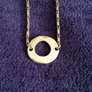 A choker necklace made with a hammered brass circle and a delicate chain.