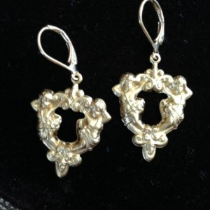 Heart filligree brass earrings dangle from brass leverbacks.