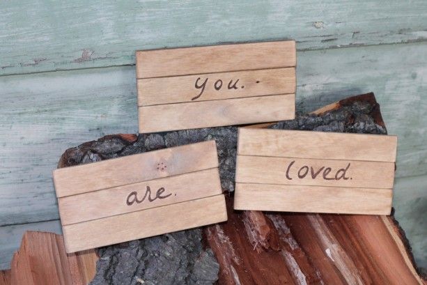 Wooden YOU ARE LOVED signs/plaques with wood burned lettering.