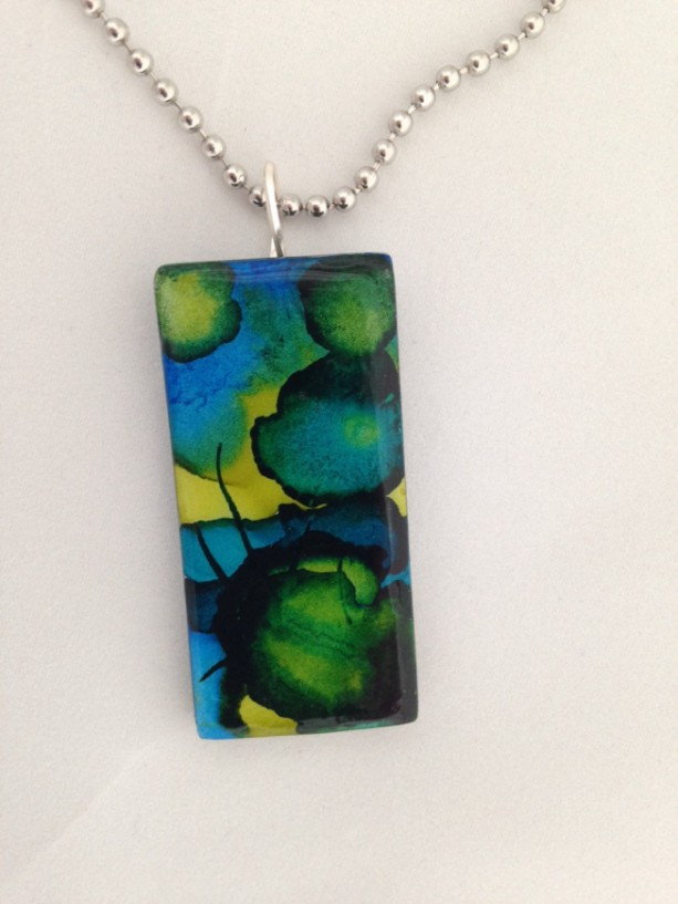 Alcohol ink painted glass pendant. Blue, green, black and gold