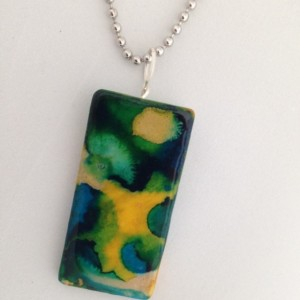Hand painted alcohol ink ceramic pendant.  Primarily green, blue and gold.