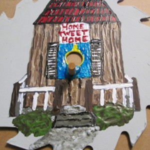 Handpainted saw blade with a birdhouse and perch